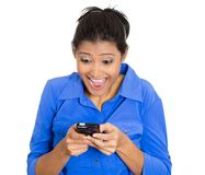 Surprised woman with phone. Closeup portrait of pretty young woman looking shocked with opened mouth and eyes on a cell phone watching sports game match or Stock Photos