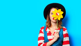 Surprised woman with pinwheel. Portrait of young suprised red-haired white european woman in hat and red striped shirt with jeans dress with yellow pinwheel on Stock Image