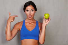 Surprised woman pointing to apple with open mouth Stock Photos