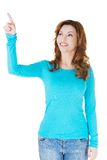 Surprised woman pointing up to the corner.  Royalty Free Stock Photo