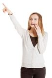 Surprised woman pointing up to the corner Royalty Free Stock Image