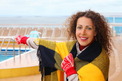 Surprised woman points to something. Surprised and happy woman wearing in red mittens and plaid points to something far at ship deck Stock Photos