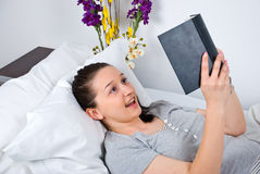 Surprised woman reading a book in bed royalty free stock image