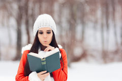 Surprised Woman Reading a Book Outside in the Snow Stock Photography