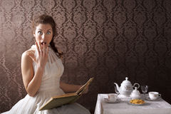 Surprised woman reading a book at tea time Stock Photo