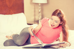 Surprised woman reading magazine laying on a bed of a hotel room Royalty Free Stock Photos