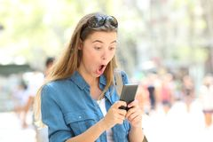 Surprised woman reading phone text in the street. Surprised woman reading online smart phone text in the street Royalty Free Stock Images