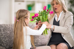 Surprised woman receives flowers from her daughter Royalty Free Stock Images