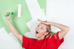 Surprised woman in red t-shirt with paint roller Royalty Free Stock Image