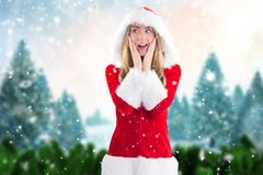 Surprised woman in santa costume standing against digitally generated background Stock Photos