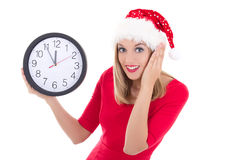 Surprised woman in santa hat with clock posing isolated on white Royalty Free Stock Image