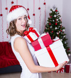Surprised woman in santa hat with gifts near Christmas tree Royalty Free Stock Photos