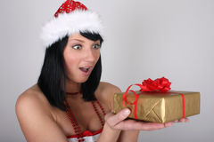 Surprised woman in santa hat with golden gift Stock Image