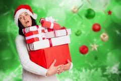 Surprised woman in santa hat holding stack of christmas gifts Royalty Free Stock Photography