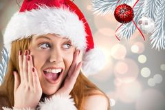 Surprised woman in Santa hat looking at Christmas decoration Royalty Free Stock Photo