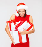 Surprised woman in santa hat with many gift boxes Stock Photography