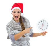 Surprised woman in Santa hat pointing on clock Stock Photos