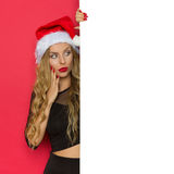 Surprised Woman In Santa Hat Reading Placard Stock Photo