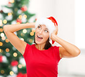 Surprised woman in santa helper hat Stock Images