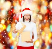 Surprised woman in santa helper hat with gift box Royalty Free Stock Image