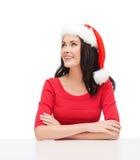 Surprised woman in santa helper hat looking up Stock Image