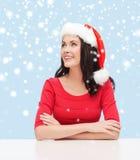Surprised woman in santa helper hat looking up Stock Images