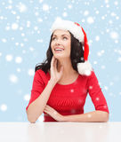Surprised woman in santa helper hat looking up Stock Photography