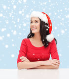 Surprised woman in santa helper hat looking up Stock Images