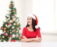 Surprised woman in santa helper hat looking up Stock Photos
