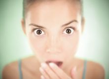 Surprised woman in shock. Closeup of a shocked woman / surprise expression. Shallow depth of field with soft focus on a green background Royalty Free Stock Photos
