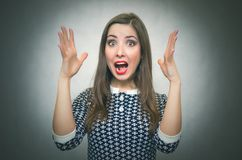 Surprised woman in shock. Winner. Surprised woman in shock is holding her hands raised up and is screaming isolated on gray background. Suddenness. Win Royalty Free Stock Images