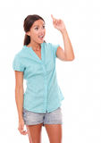 Surprised woman in short jeans pointing up Stock Photo