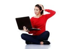 Surprised woman sitting cross-legged with laptop Stock Image