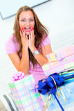 Surprised woman sitting among gifts Stock Photo