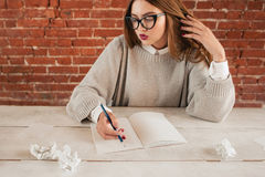 Surprised woman sitting at table with notebook Royalty Free Stock Images