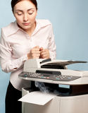 Surprised woman with smoking copier Royalty Free Stock Images
