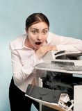 Surprised woman with smoking copier Stock Image