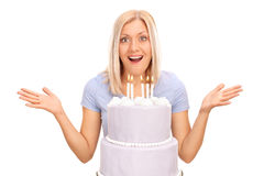 Surprised woman standing behind a birthday cake Stock Photography