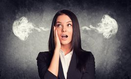 Surprised woman with steam from ears. Concrete Royalty Free Stock Images