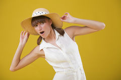 Surprised woman in summer hat. Over yellow background Stock Image
