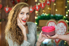 Surprised woman takes gift in box with heart shaped Stock Images