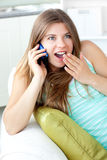 Surprised woman talking on phone lying on the sofa Royalty Free Stock Images
