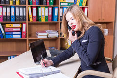 Surprised woman talking on phone in office Stock Photo
