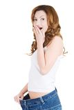Surprised woman in too big jeans Stock Photography