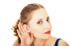 Surprised woman trying to listening a gossip Stock Photo
