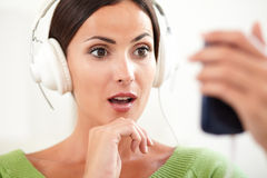 Surprised woman using a portable music player Stock Photos