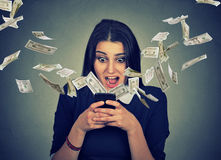 Surprised woman using smartphone dollar bills flying away from screen Stock Photo