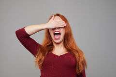 Surprised woman waiting for something with closed eyes. Close-up portrait of surprised young woman with red hair waiting for something with closed eyes. Isolated Stock Photo
