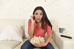Surprised woman watching television sitting at sofa couch excited enjoying thriller movie. Young beautiful Spanish woman in jeans home alone watching television Royalty Free Stock Photos