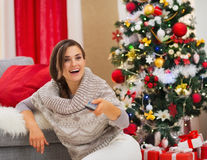 Surprised woman watching TV near Christmas tree Royalty Free Stock Photography